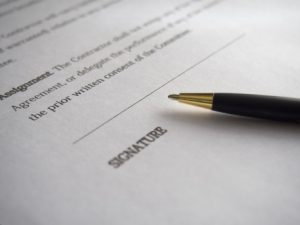 close up of a pen sitting on a contract