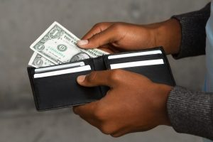close up of man's hands pulling dollar bills out of a wallet