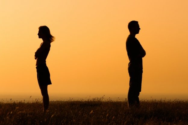 silhouette of couple facing away from each other in a field